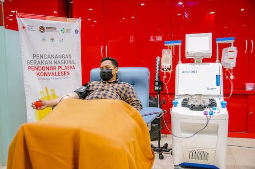 Pendonor sedang donor plasma konvalesen dengan mesin apheresis